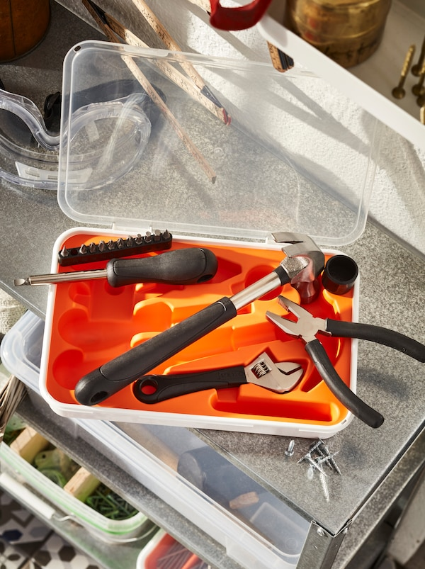 An open FIXA toolbox, tools halfway out, lies on top of a metal, open-shelf cabinet holding boxes of home-fixing accessories.