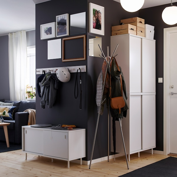 An open hall with a dark grey color on the wall with enough closets and hooks for your jacket, bag and keys.
