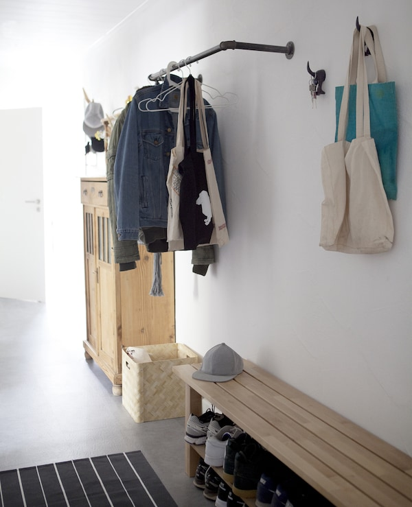 An open hallway with a bench, rail, hooks and cabinet.