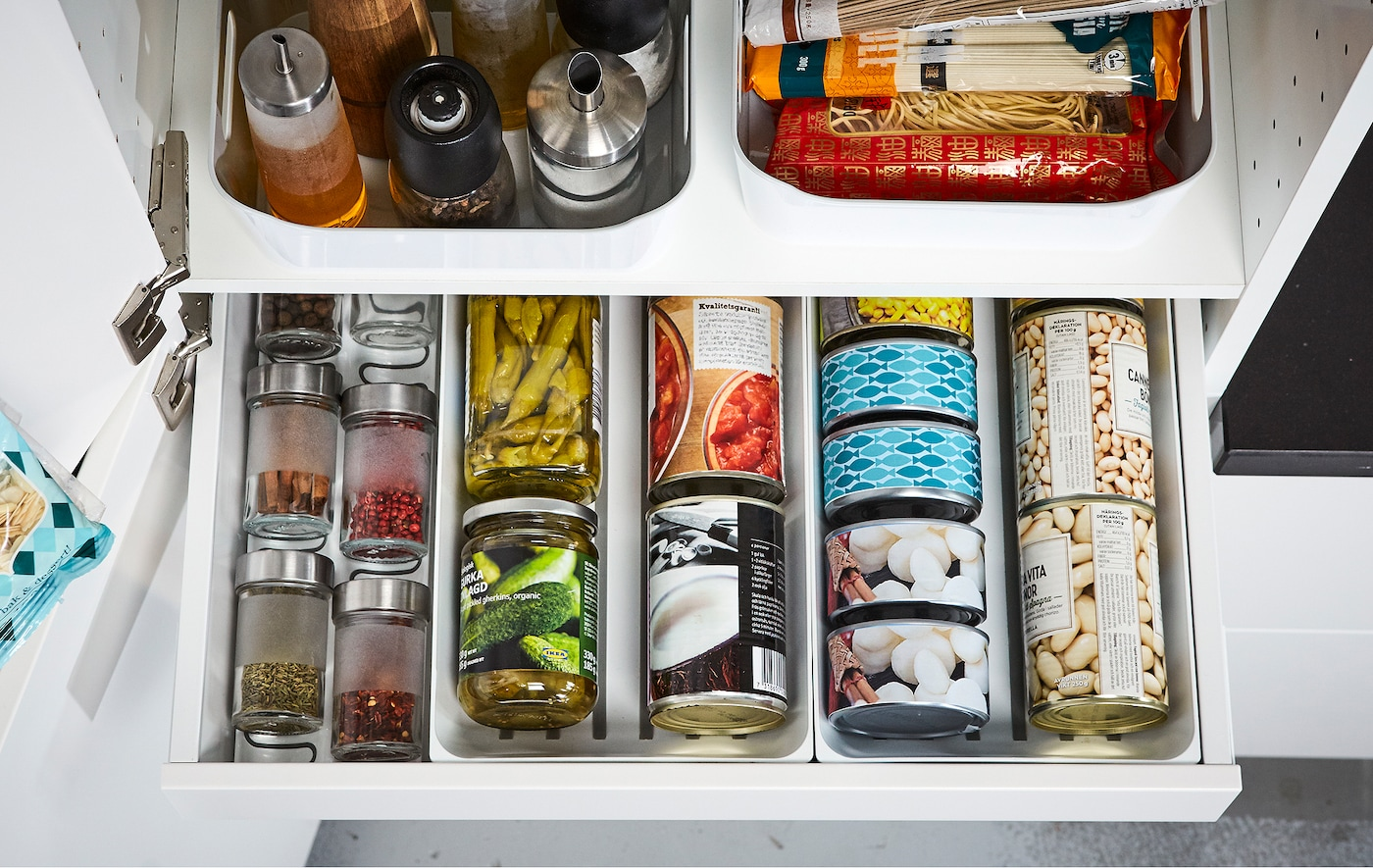 An open IKEA MAXIMERA white kitchen pantry drawer displaying organized cans, spices and oils.