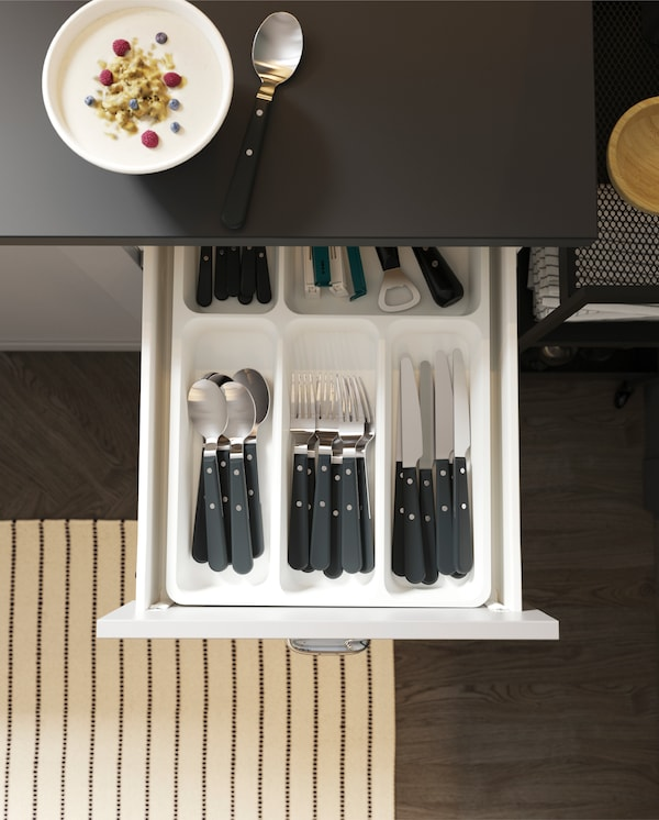 An open kitchen drawer with a cutlery tray with organised cutlery and kitchen utensils, a striped rug and a bowl of yoghurt.