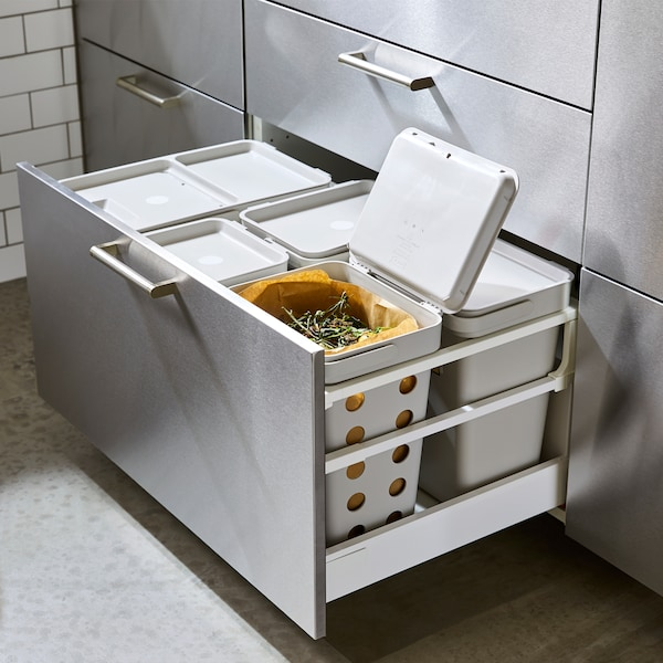 An open kitchen drawer with a front in stainless steel. Grey waste sorting bins are inside and one has ventilation holes.
