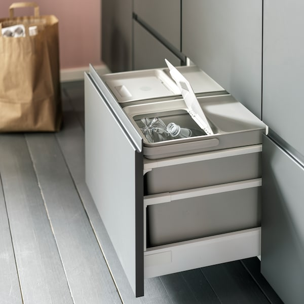An open kitchen drawer with light grey waste sorting bins inside. One lid is open and plastic bottles are sorted inside.