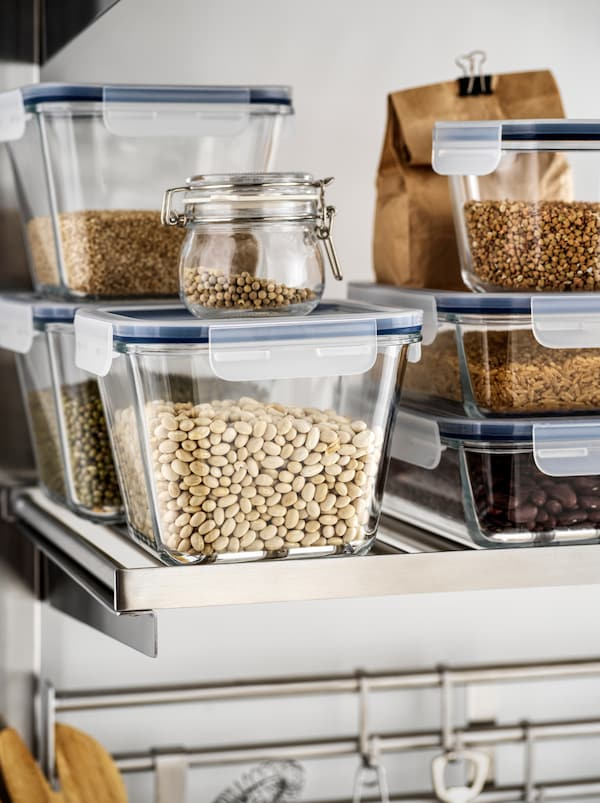 An open kitchen shelf with transparent IKEA 365+ glass containters filled with beans stacked onto each other.