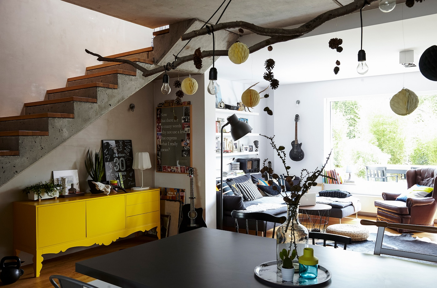 An open living space, leading to an outside terrace, with tree branches and decorations hanging from the ceiling.