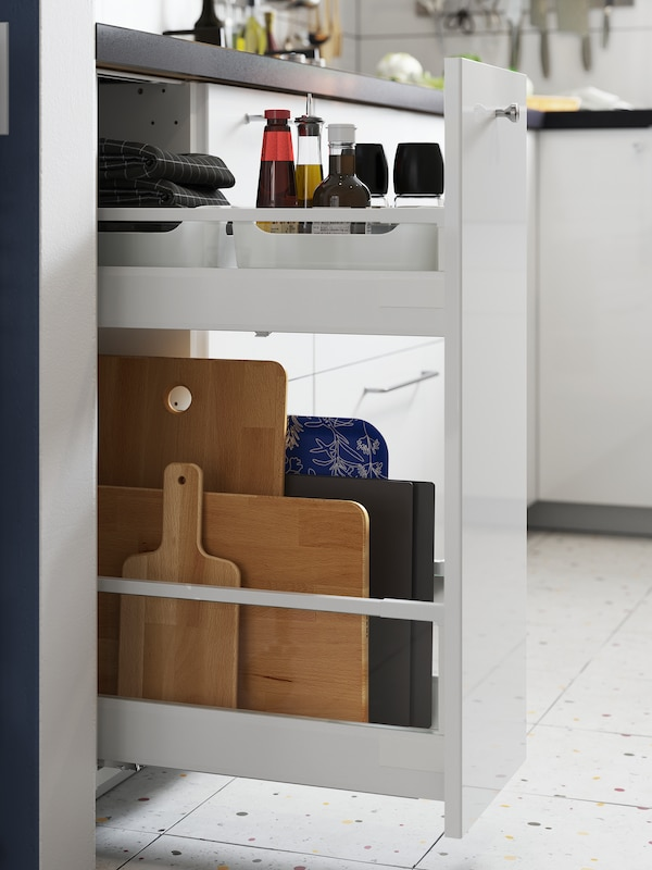 An open narrow pull-out cabinet with chopping boards on the lower shelf and oils and condiments on the upper one.