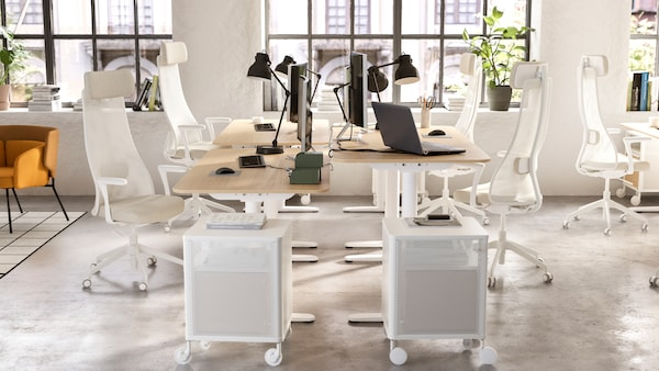 An open office space with 4 desks, 4 office chairs and 4 work lamps.
