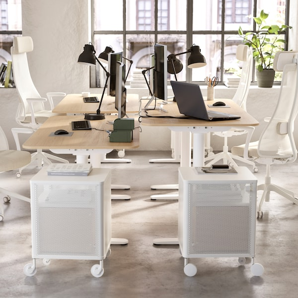 An open office space with four desks, four office chairs, four work lamps and two drawer units.