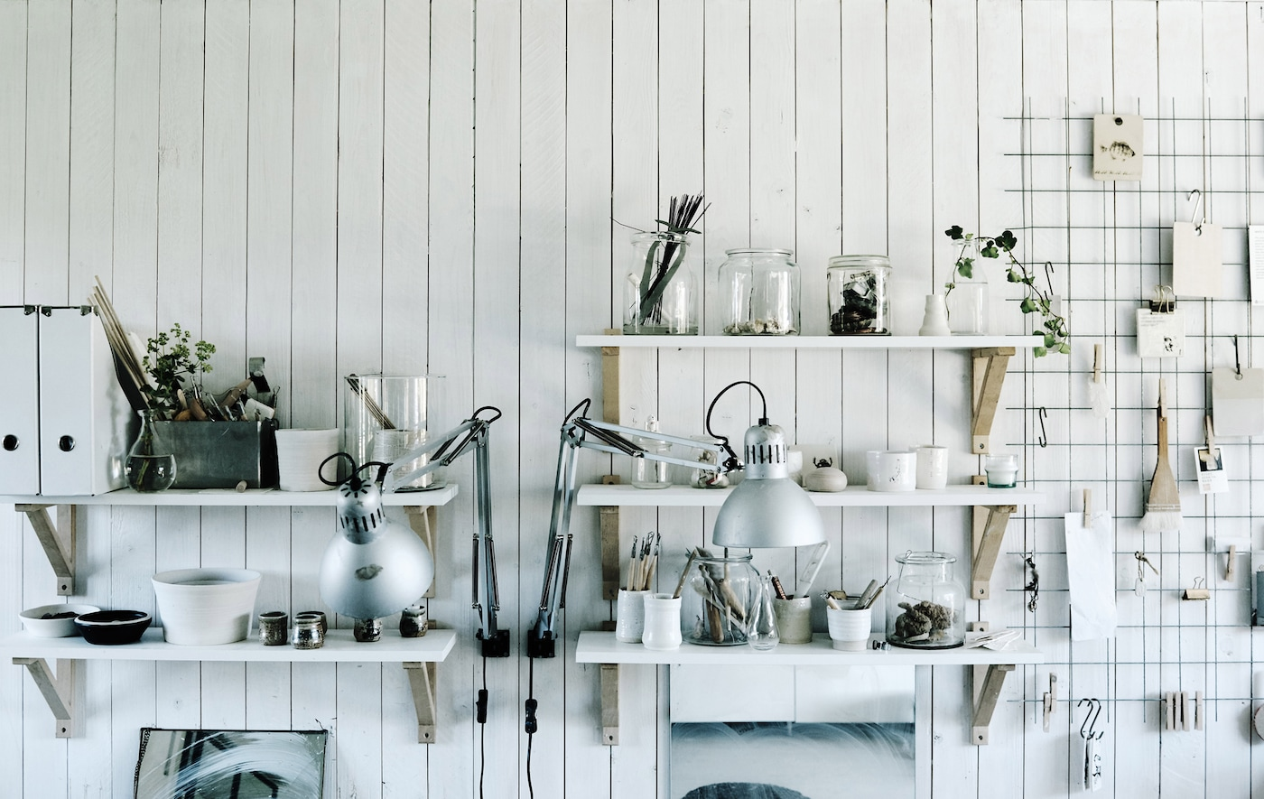 An open pantry with white shelves that hold clear jars and glassware and a wire rack with clip-on utensils and papers.