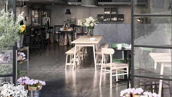 An open plan cafe, shop and co-working space framed by open glass doors. Flowers are on the table and by the doors.