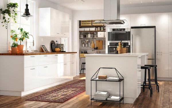 An open plan kitchen with a kitchen island that combines white RINGHULT doors in high gloss with a SKOGSÅ oak worktop.