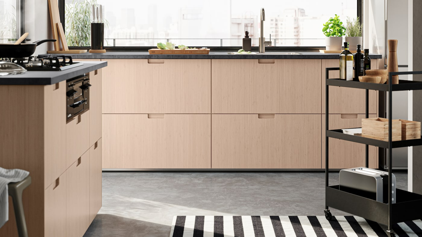 An open-plan kitchen with FRÖJERED fronts in light bamboo. There is a NISSAFORS trolley with condiments, boxes and a toaster.
