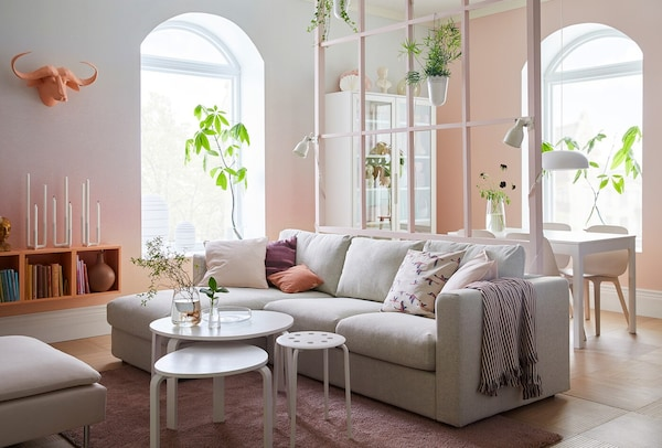 An open plan living and dining room with beige sofa and orange and pink accessories.