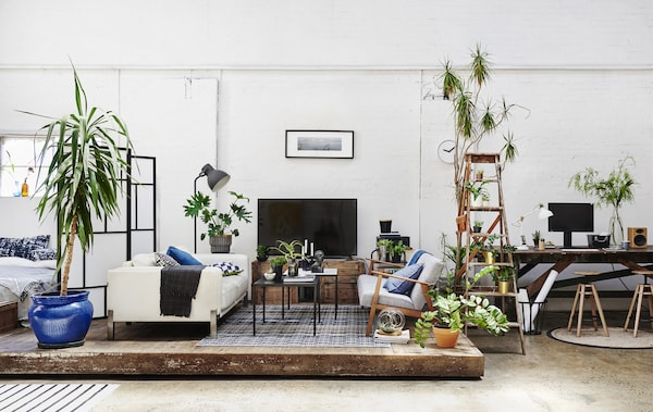 An open-plan living room and work space with high ceilings and a wooden platform.