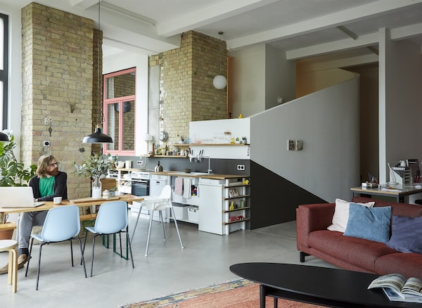An open-plan living room, kitchen, and dining space in a converted loft with brick walls.