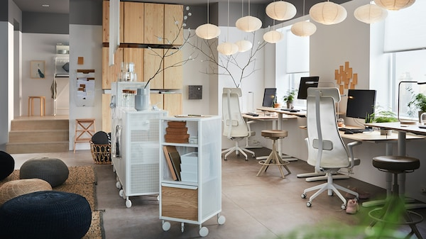 An open-plan office featuring an area with comfy office chairs around desks, drawer units and storage units
