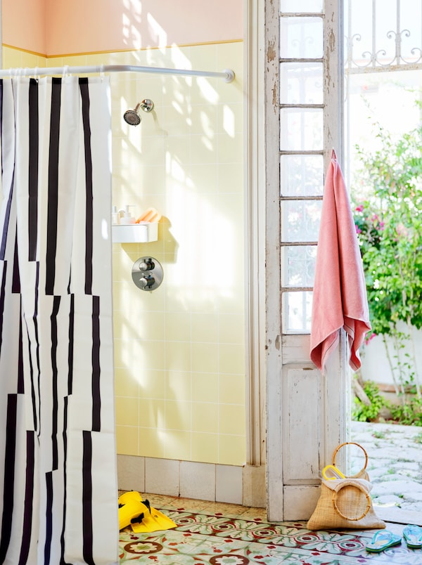 An open shower with a black and white shower curtain, next to an open white-washed wooden door.