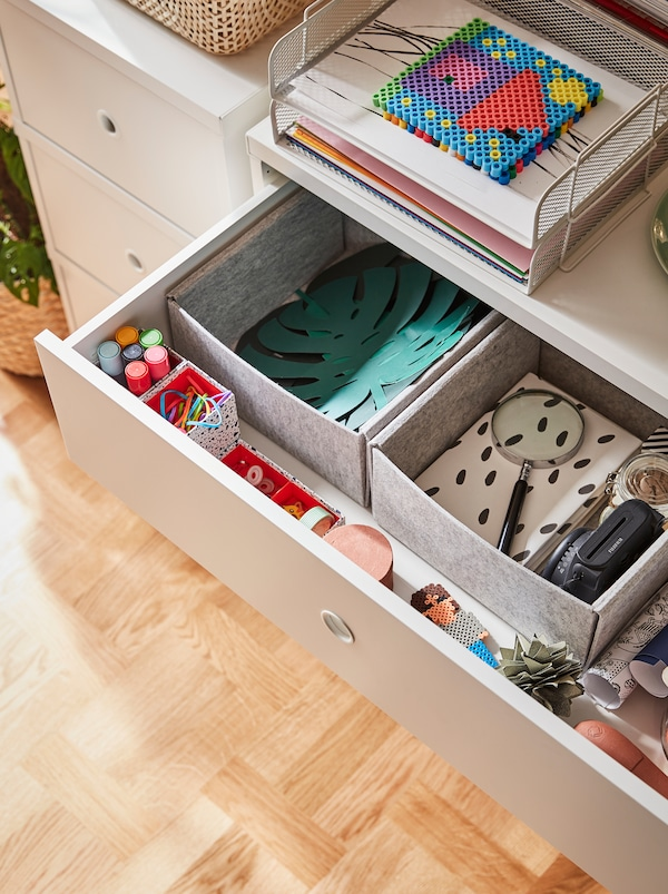 An open top drawer of a chest of drawers reveals paper and drawing accessories organised in KOMPLEMENT boxes.