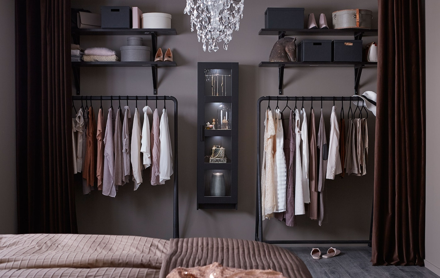 An open wardrobe consisting of black hanging racks, black open shelves and a black display cabinet, filled with clothes.