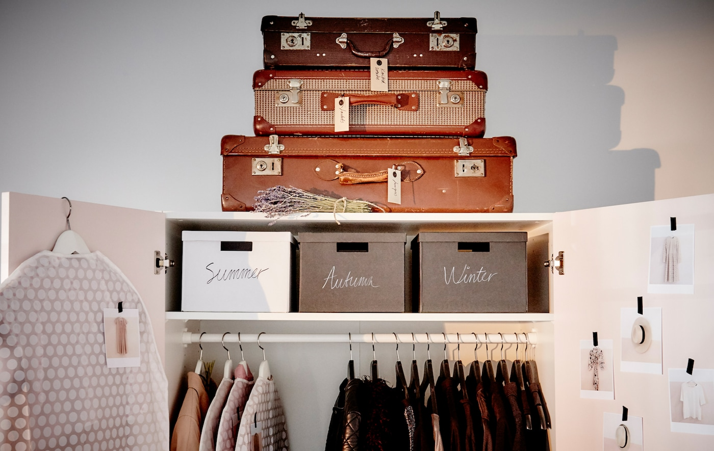 An open wardrobe with clothes on a rail, boxes on a shelf, and a stack of vintage suitcases on top.
