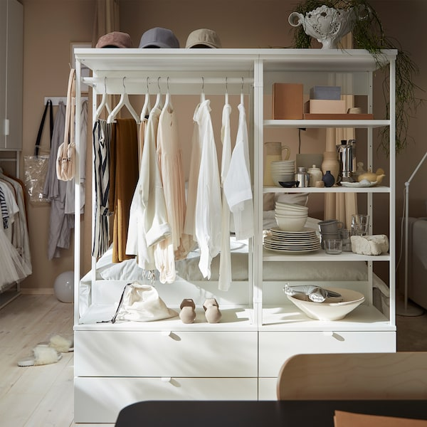 An open wardrobe with drawers, shelves and a rail. Clothes hang on white hangers, and decorative items stand on the shelves.