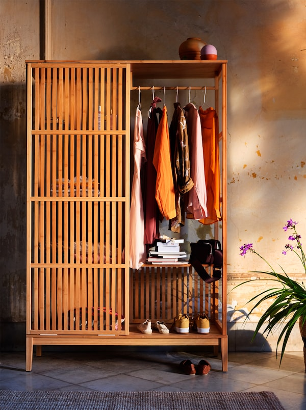 An open, wooden wardrobe with sliding doors filled with autumn-coloured clothing, placed against an orange-yellow wall.