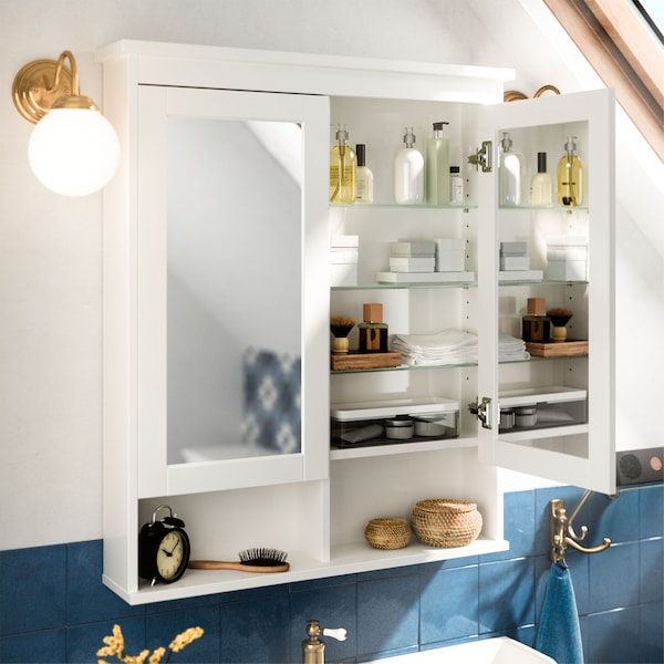 An opened IKEA HEMNES white mirror cabinet, revealing glass shelves, mirrors on both sides of the door and bathroom accessories.