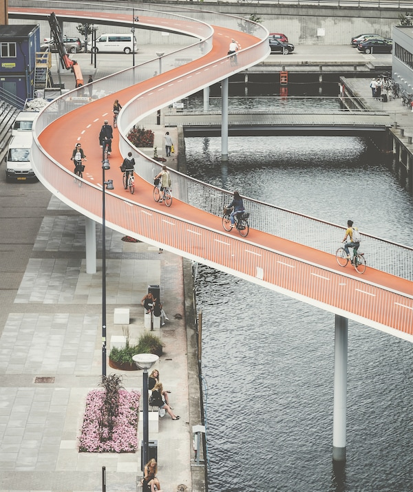 An orange cycle bridge winds above a river and pavement.