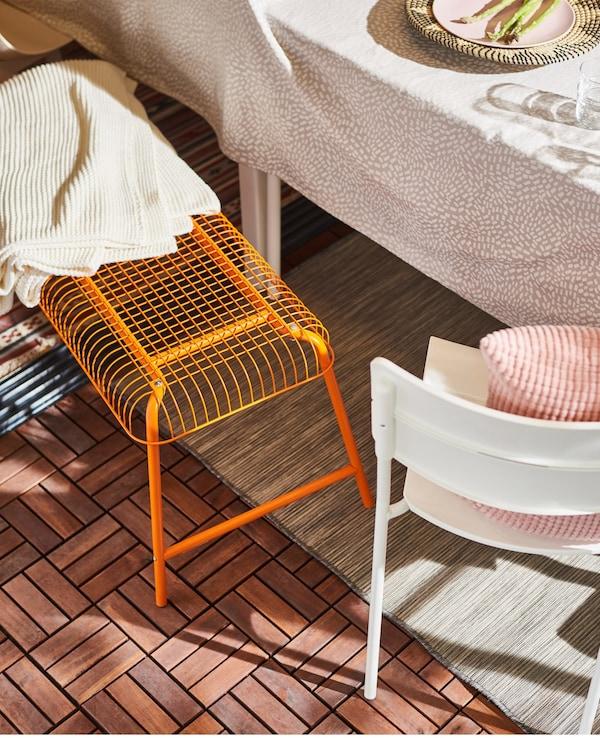 An orange IKEA VÄSTERÖN bench next to a dining table outside.