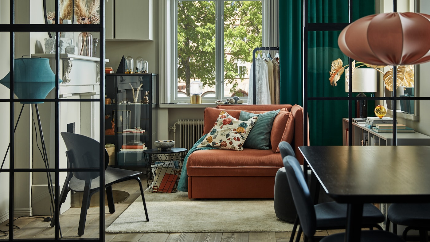 An orange sofa bed in the middle of a living room with grey walls, green curtains, a glass door cabinet and a beige rug.