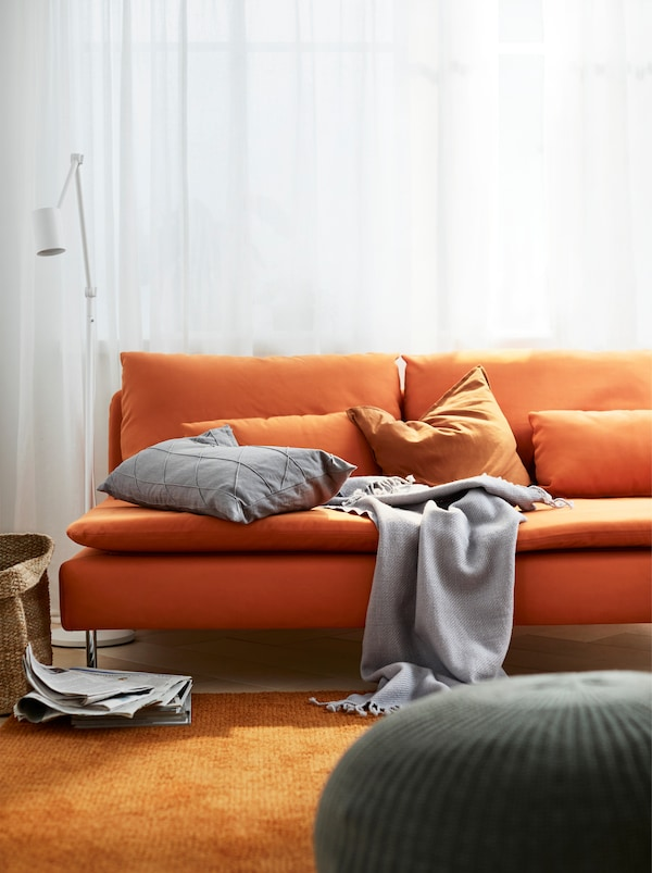An orange three-seat SÖDERHAMN sofa with pillows and a cover standing in a living room with a big orange rug.
