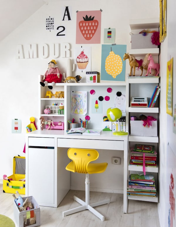An organised children's work station where the colourful art and toys bring style to the all-white room.