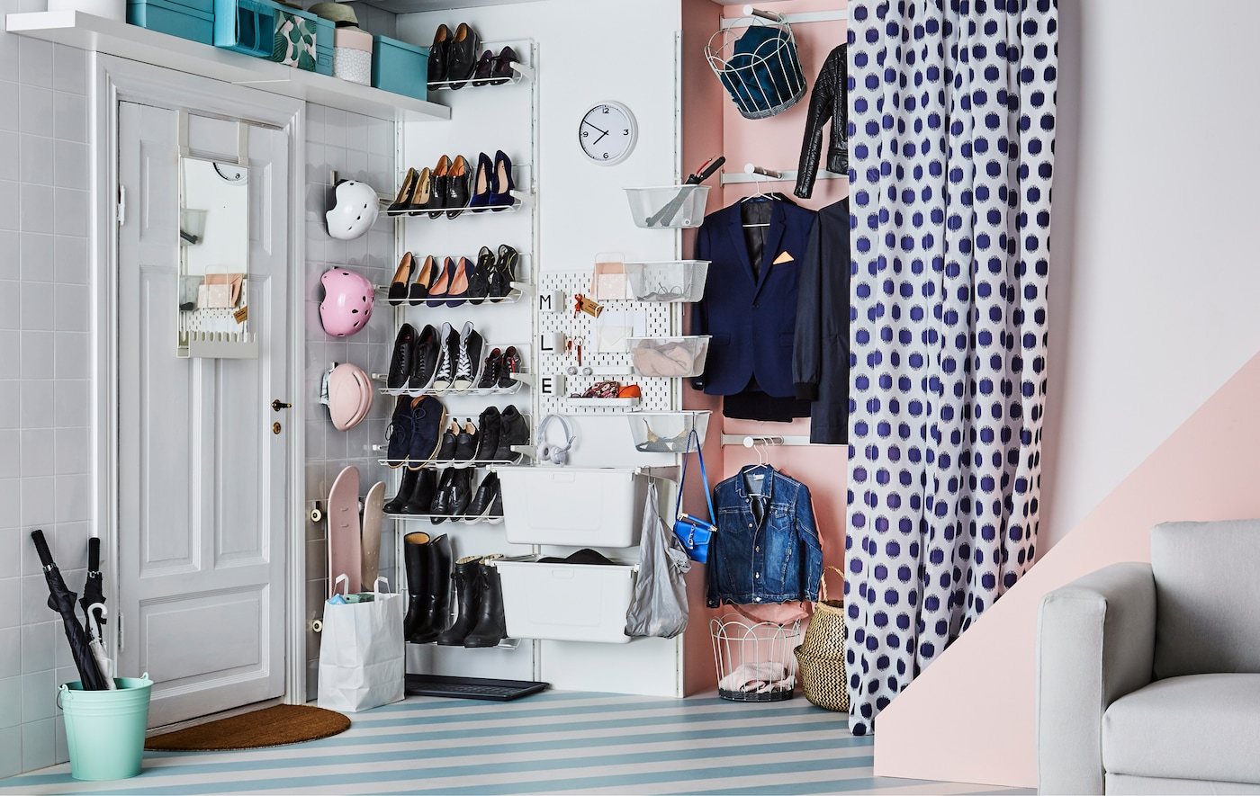 An organised hallway by the door filled with shoes and coats and things for a family of three