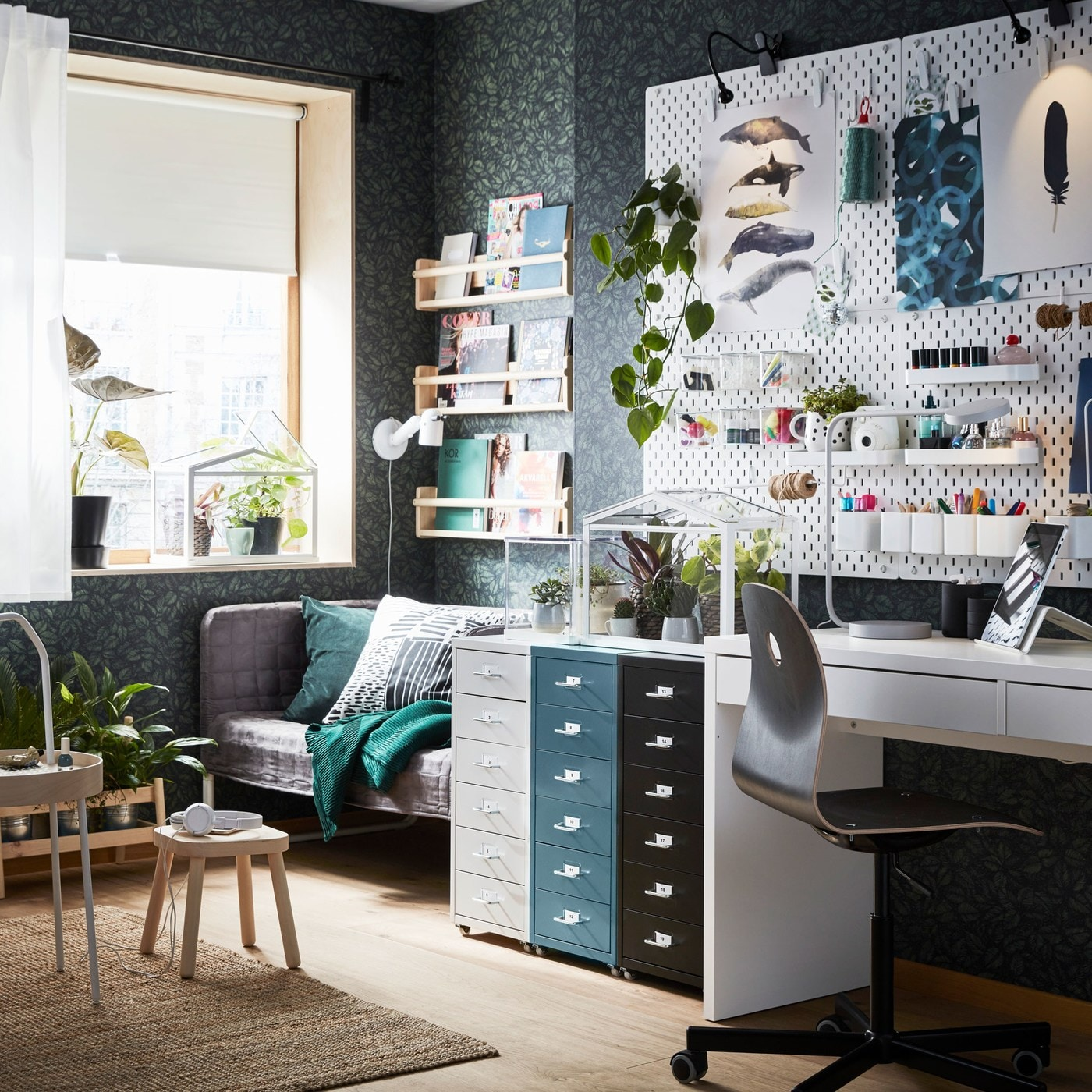 An organised home workspace with dark wallpaper has a white pegboard and three HELMER drawer units on castors.