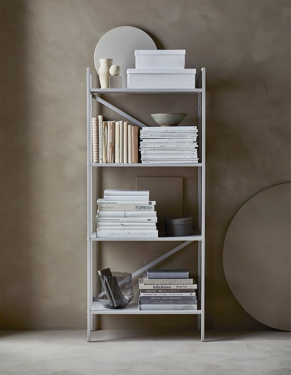 An organised, open shelving unit that holds storage boxes, books, magazines and decorative objects.