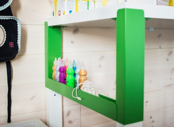 An organised study area for a child that uses a white and green PÅHL desk, a desk shelf unit and see-through boxes with lids.