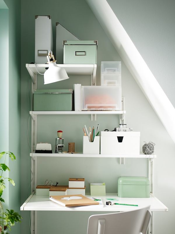 An organised work station under a sloped ceiling, made using IKEA wall storage with shelves of different widths.