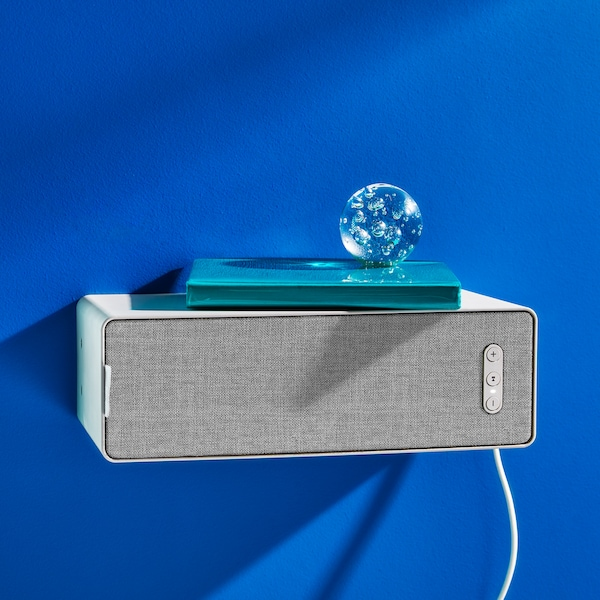 An ornamental glass globe sits on top of a book which is on top of a white SYMFONISK WiFi bookshelf speaker.