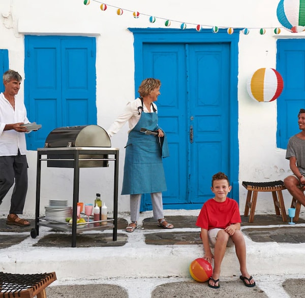 An outdie BBQ with a family in front of blue doors and white walls.