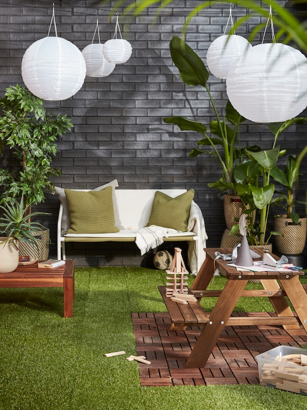 An outdoor area with a cosy seating area, lush plants, SOLVINDEN LED solar-powered pendant lamps against a grey brick wall.
