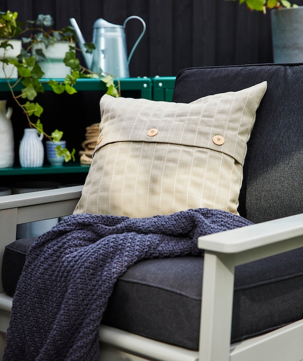 An outdoor chair with dark blue cushions shown with and an extra pillow in beige and a dark blue blanket.