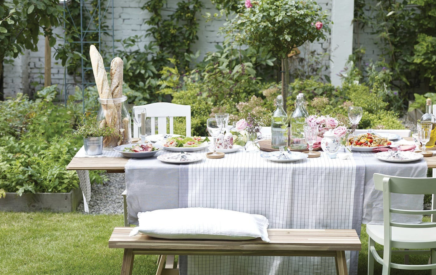 An outdoor dining table dressed with tableware, glassware and food.