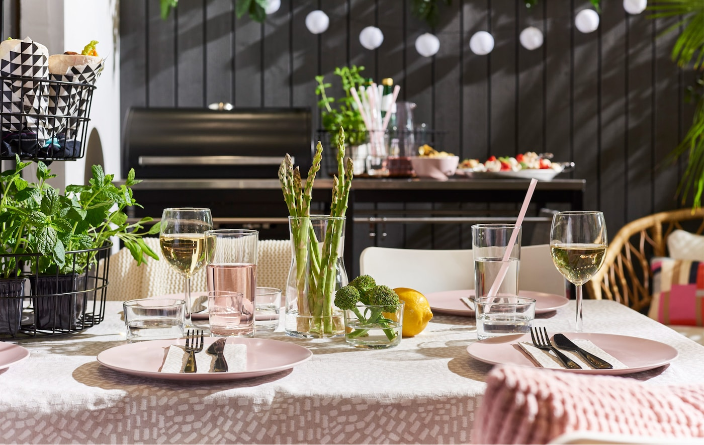 An outdoor dining table set with seasonal table settings and pink dishes and tablecloth