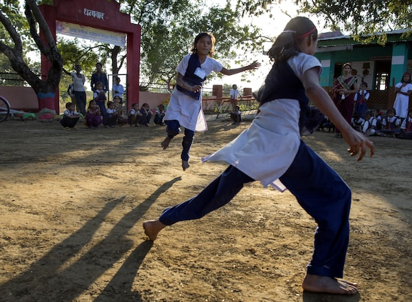 An outdoor evening scene in an Eastern country where girls are running around playing in the schoolyard.