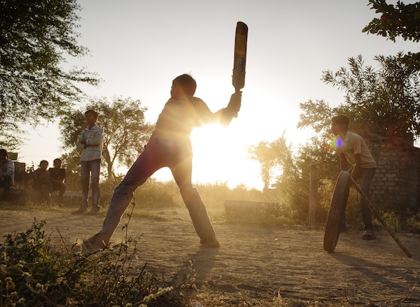 An outdoor evening scene in the countryside with several teenagers playing a baseball-like game.