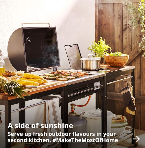 An outdoor grill is set up with accessories and food to create a summer meal.