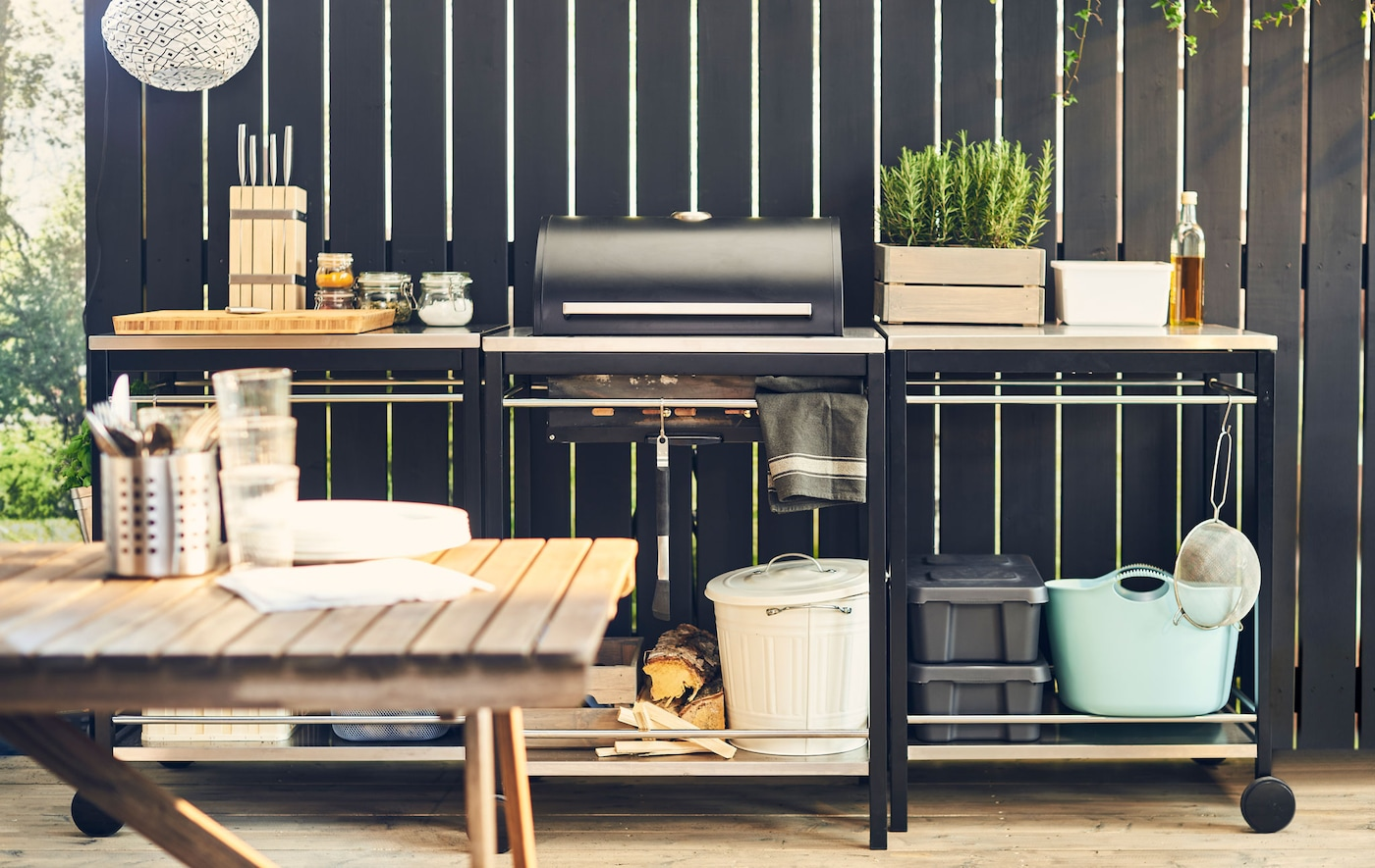 An outdoor kitchen made up of three units, including a grill, stands against a black wooden fence.