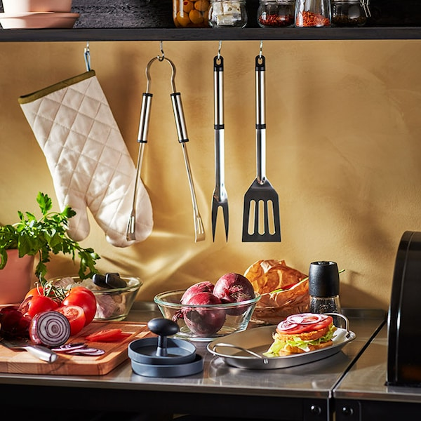 An outdoor kitchen with vegetables, a hamburger press, a tray with a hamburger, and barbecue tools hanging above.