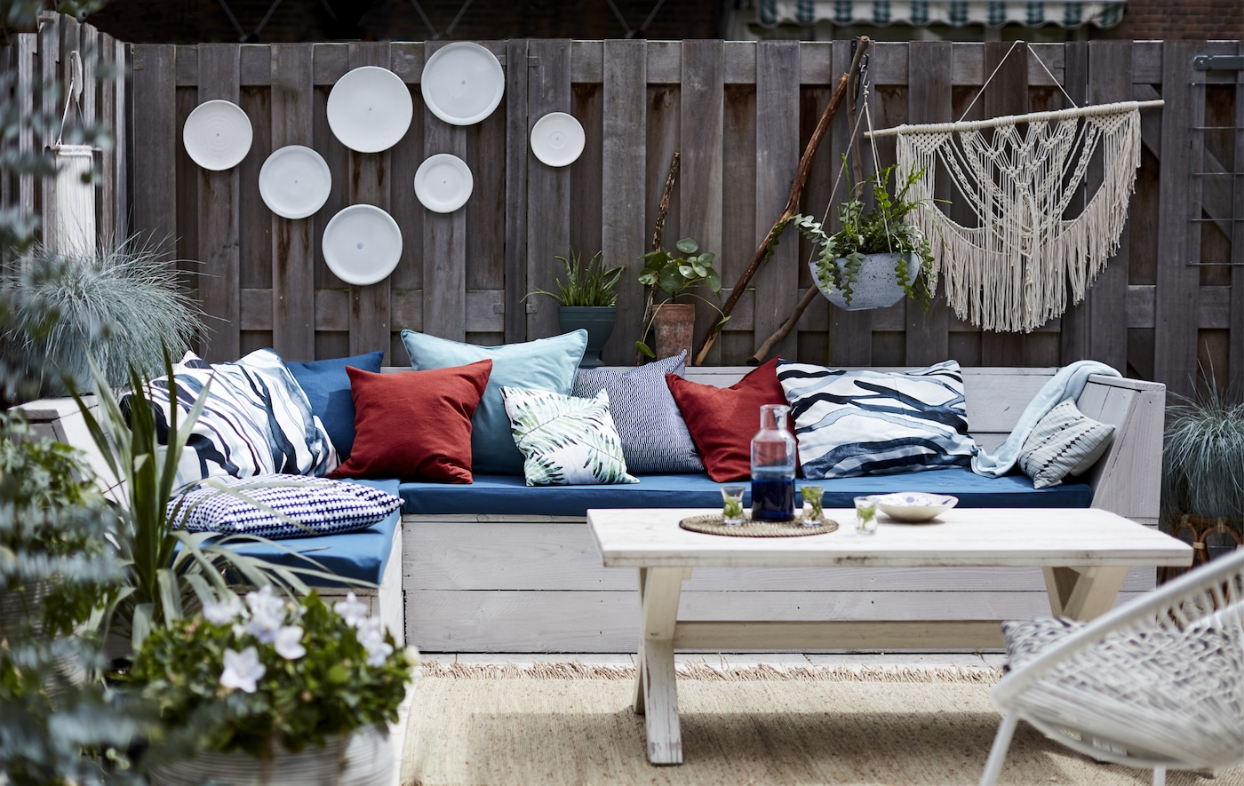 An outdoor living room with cushions and hanging plants.