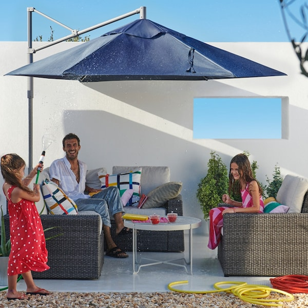An outdoor patio space with a man and two children sitting on an outdoor lounge set with a large outdoor umbrella overhead.